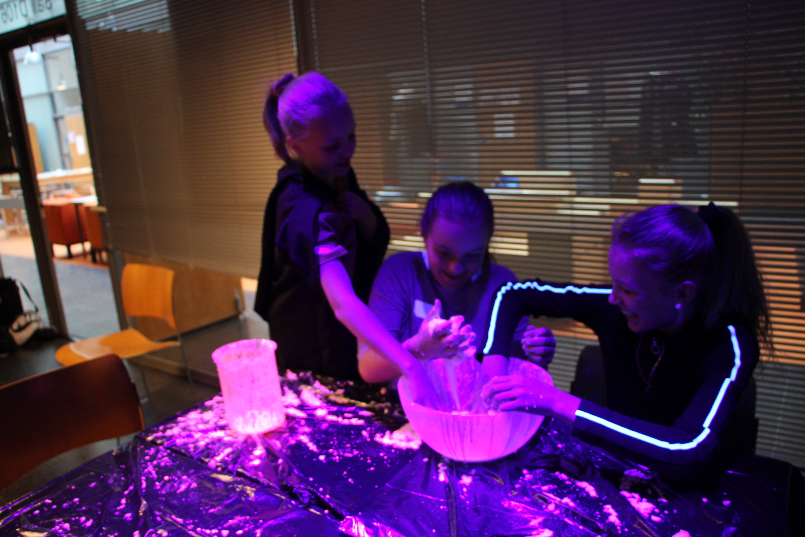 Girls doing chemistry experiments in UV-light