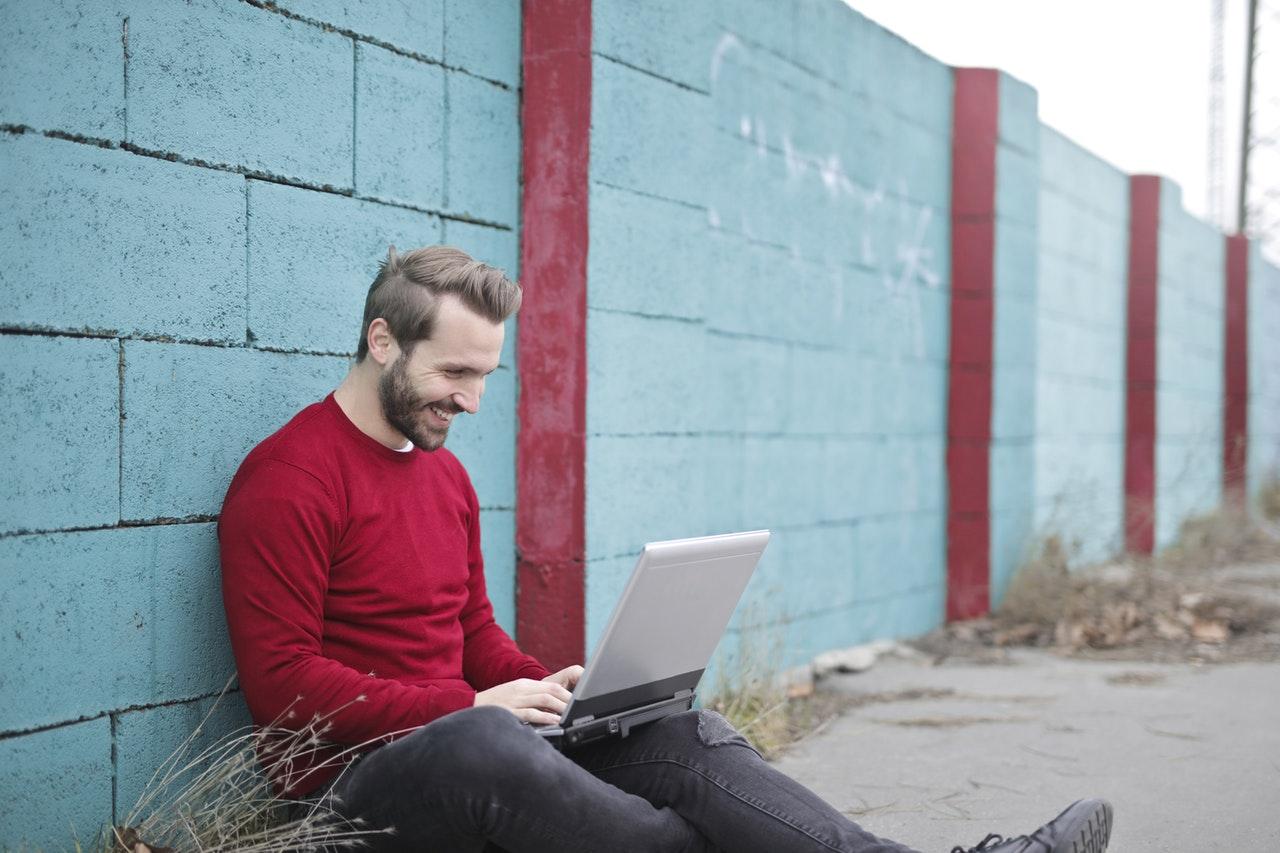 en man sitter utomhus vid en dator