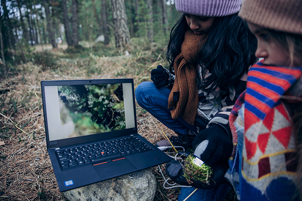 Två flickor forskar naturen med hjälp av en dator.