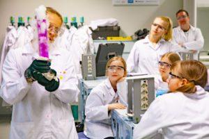 Tiedekasvatuksen ohjaaja esittelee tiedekerhoon osallistuville tytöille tiedekoneen tuloksia.