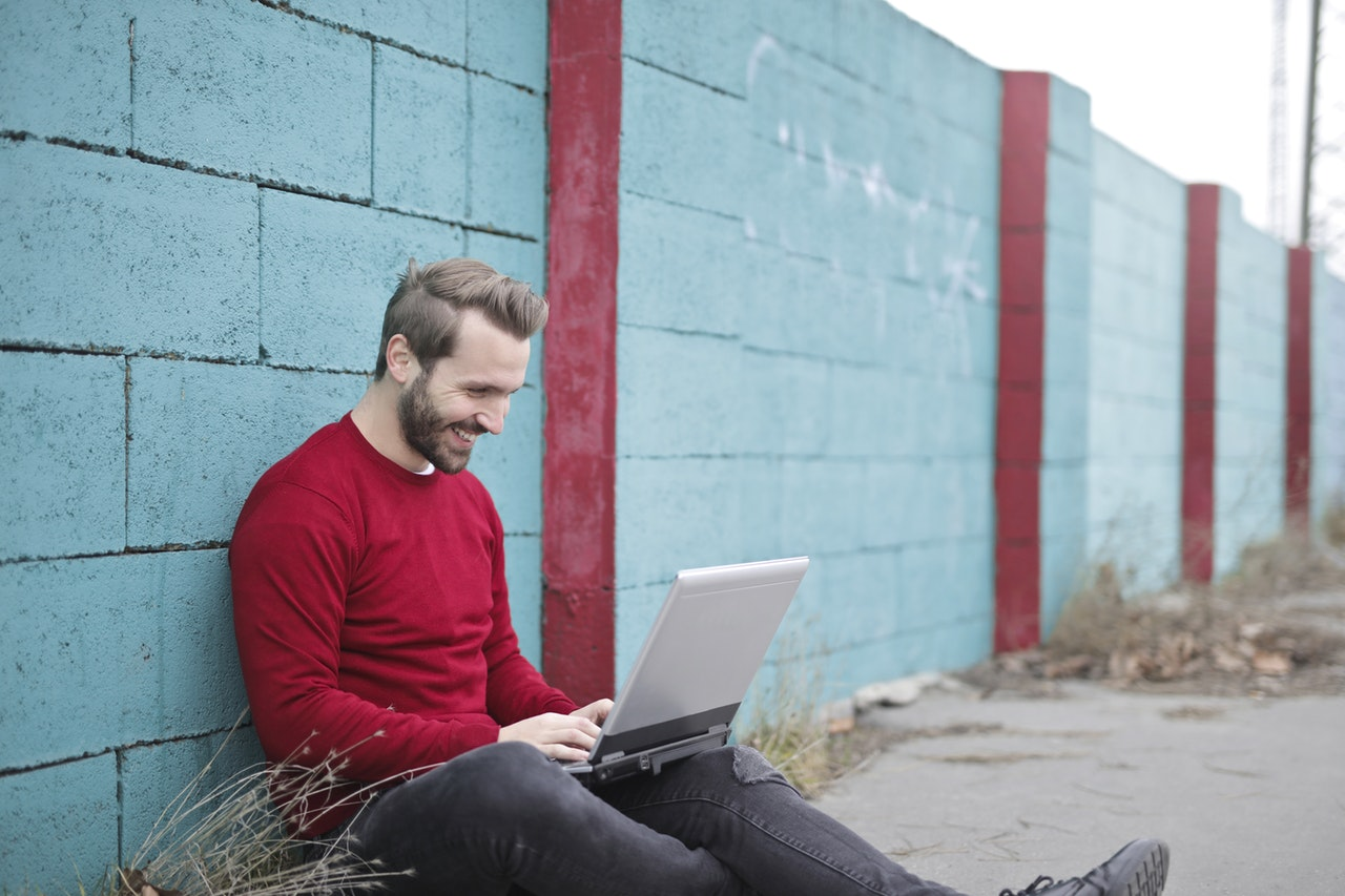 hymyilevä mies istuu ulkona tietokoneen äärellä