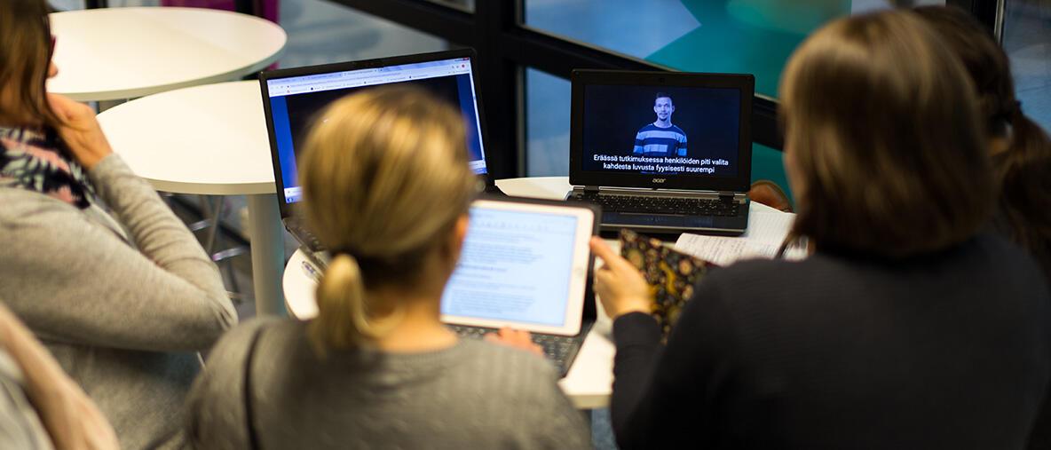 Opettajia tekemässä ryhmätyötä selin tietokoneen edessä