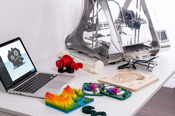 tietokone ja 3D-tulostettuja esineitä pöydällä