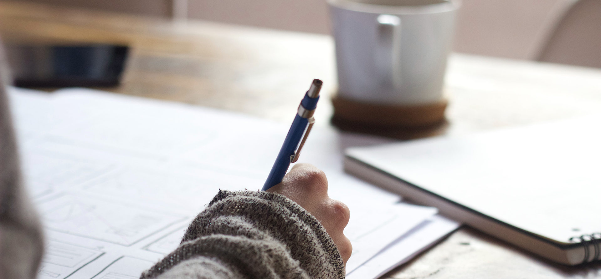 Henkilö kirjoittaa kynällä paperille. Taustalla on kahvikuppi.