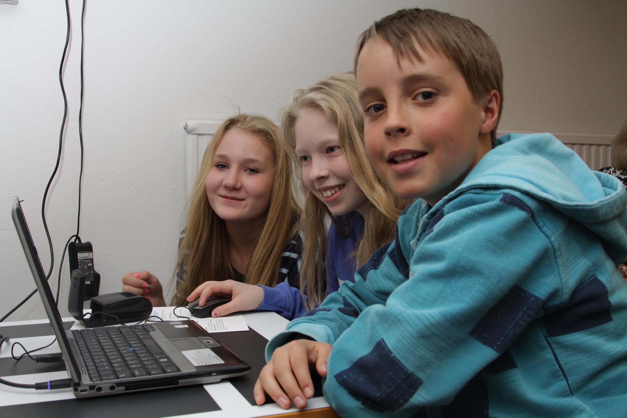 kolme iloista lasta tietokoneen äärellä.