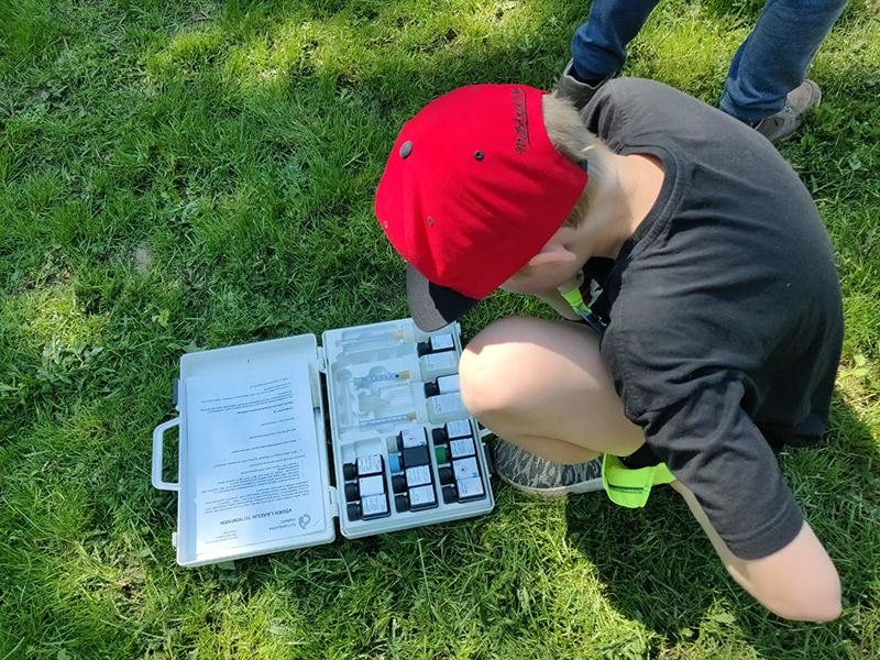 Poika tutkii kumartuneena annettua tehtävää tiedeleirillä kesällä 2019.
