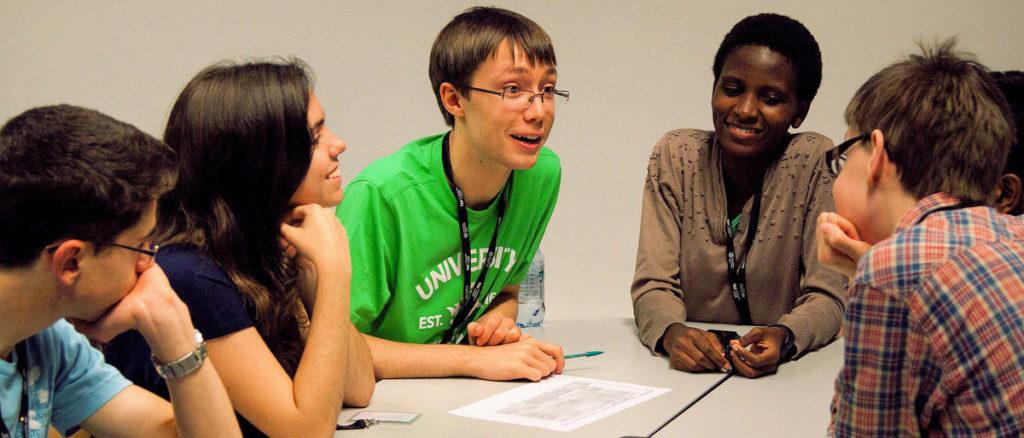 Joukko nuoria keskustelee yhdessä kansainvälisellä Global Challenges -leirillä. Leiri on esimerkki lukioikäisille suunnatusta toiminnasta