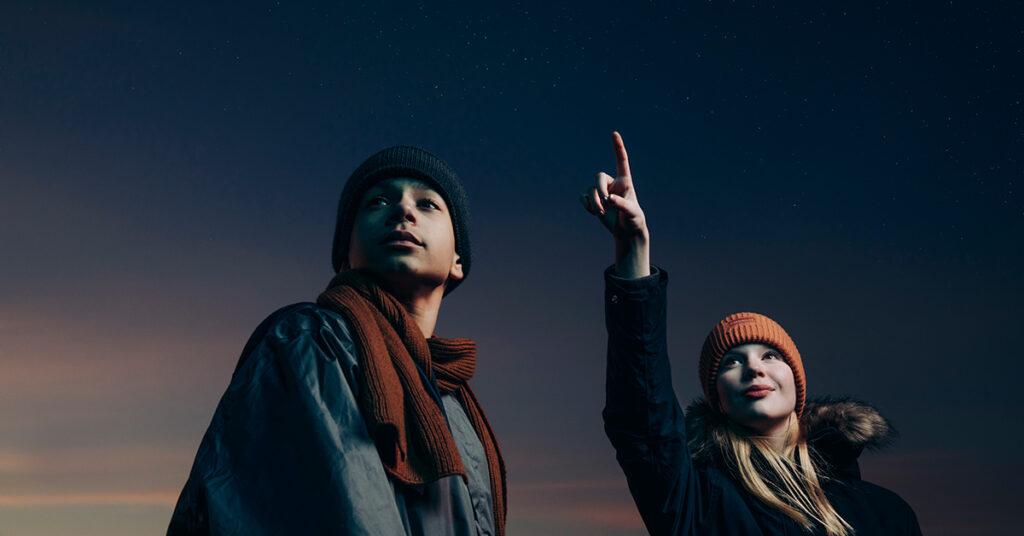 Kaksi nuorta tutkii taivasta. Toinen heistä osoittaa taivaalle.